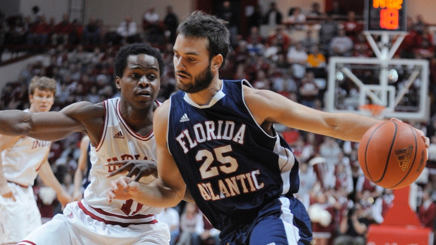 Indiana's Kevin Ferrell defends as Florida Atlantic's Pablo Bertone drives to the basket during the first half of an NCAA college basketball game in Bloomington, Ind., Friday, Dec. 21, 2012. (AP Photo Alan Petersime)
