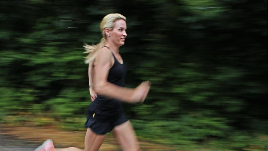 In this photo taken July 17, 2012  Suzy Favor Hamilton runs at her home in Shorewood Hills a suburb of Madison, Wis. The three-time Olympian has admitted leading a double life as an escort. She apologized Thursday, Dec. 20, 2012, after a report by The Smoking Gun website said she had been working as a prostitute in Las Vegas. (AP Photo/Milwaukee Journal-Sentinel, Michael Sears)