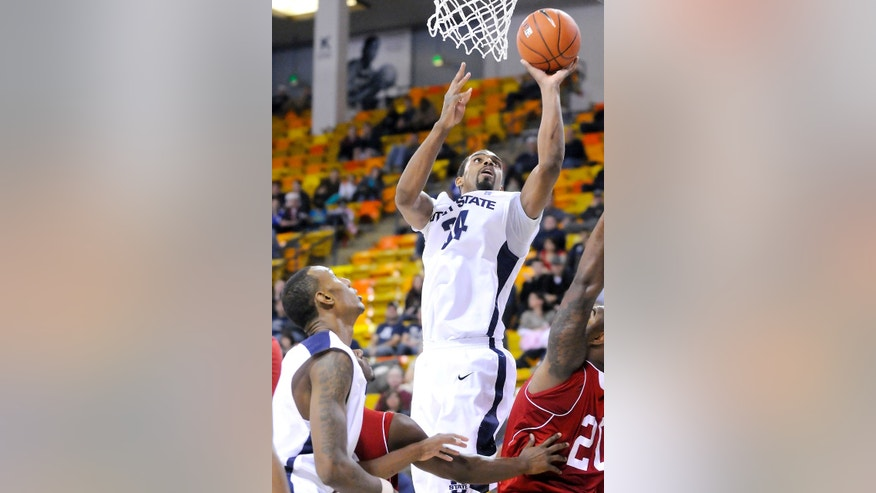 Utah State forward Kyisean Reed (34) takes a shot over Nicholls State guard Fred Hunter (20) as center Jarred Shaw watches during their game in the World Vision Basketball Challenge, Thursday, Dec. 20, 2012, in Logan, Utah. (AP Photo/The Herald Journal, Eli Lucero)