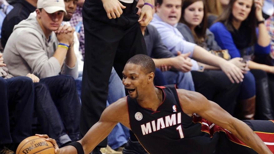Miami Heat center Chris Bosh (1) reaches for a loose ball during the first quarter of an NBA basketball game against the Dallas Mavericks, Thursday, Dec. 20, 2012, Dallas. (AP Photo/LM Otero)