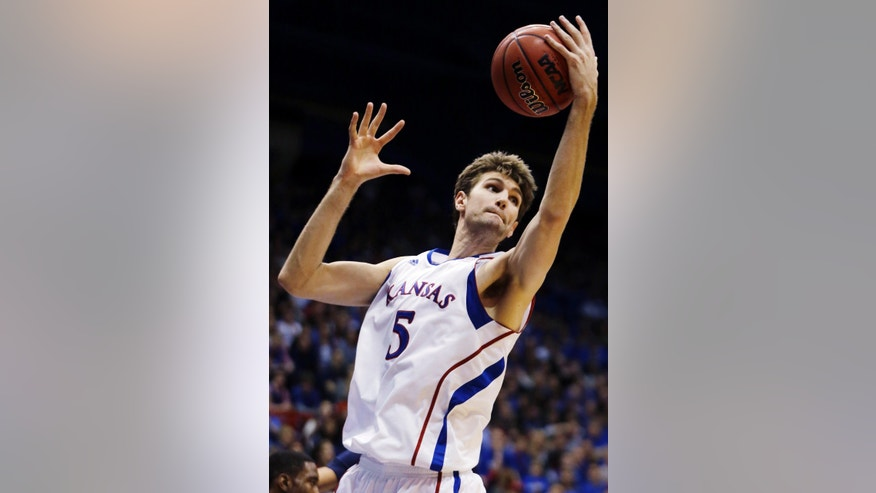 Kansas center Jeff Withey (5) rebounds during the second half of an NCAA college basketball game against Richmond in Lawrence, Kan., Tuesday, Dec. 18, 2012. Withey scored 17 points and had 13 rebounds in their 87-59 win. (AP Photo/Orlin Wagner)