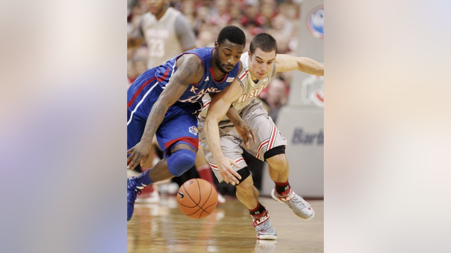Ohio State's Aaron Craft (4 )scrambles for a steal against Kansas' Elijah Jounson (15) during the first half of an NCAA college basketball game Saturday, Dec. 22, 2012, in Columbus, Ohio. (AP Photo/Mike Munden)