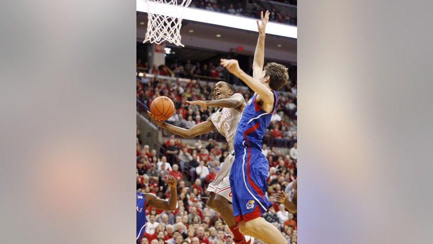 Ohio State's Sam Thompson (12) scores in front of Kansas' Jeff Withey (5) during the first half of an NCAA college basketball game Saturday, Dec. 22, 2012, in Columbus, Ohio. (AP Photo/Mike Munden)