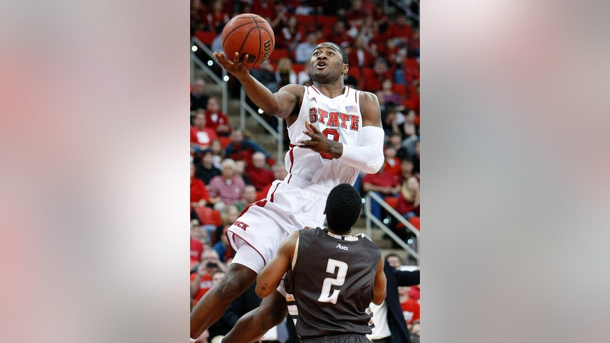 North Carolina State's Rodney Purvis (0) drives to the basket over St. Bonaventure's Eric Mosley (2) during the first half of an NCAA college basketball game in Raleigh, N.C., Saturday, Dec. 22, 2012. (AP Photo/Karl B DeBlaker)