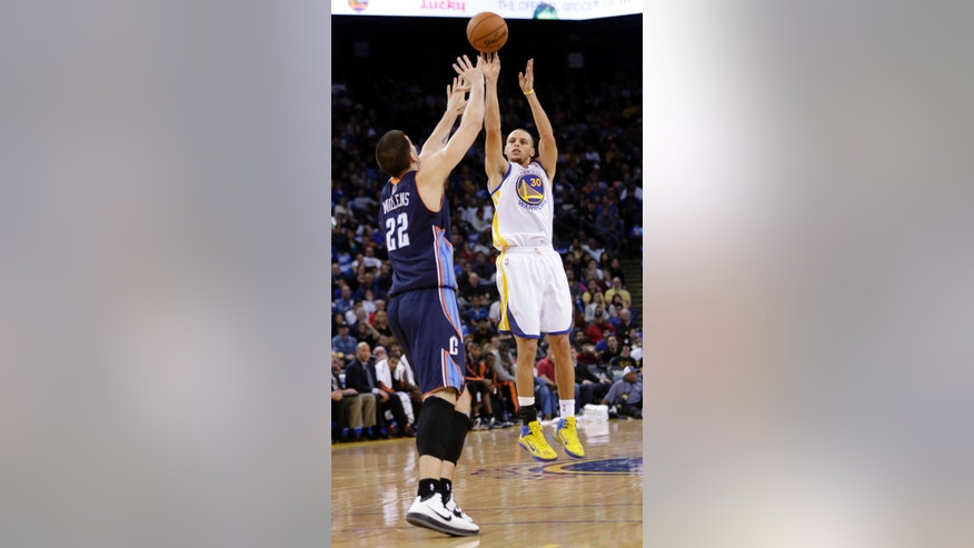 Golden State Warriors' Stephen Curry (30) shoots over Charlotte Bobcats' Byron Mullens (22) during the first half of an NBA basketball game in Oakland, Calif., Friday, Dec. 21, 2012. (AP Photo/Marcio Jose Sanchez)