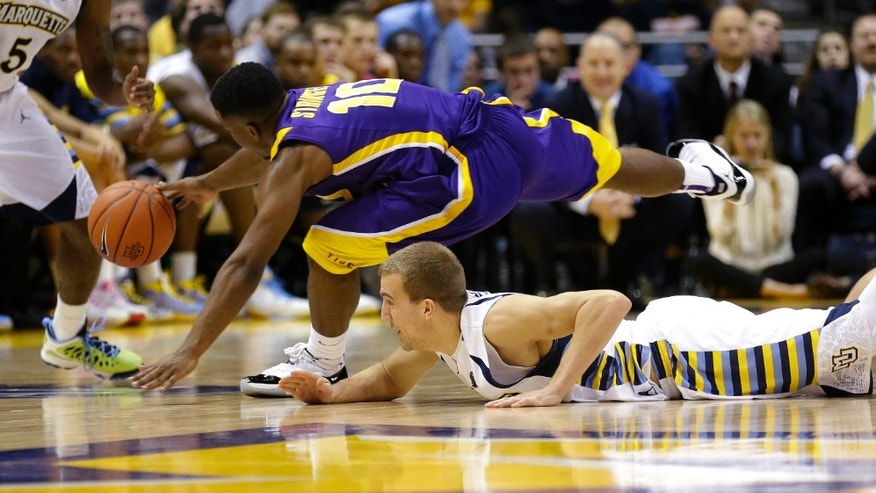 LSU's Andre Stringer(10) and Marquette's Jake Thomas dive for the loose ball during the second half of an NCAA college basketball game, Saturday, Dec. 22, 2012, in Milwaukee. (AP Photo/Jeffrey Phelps)