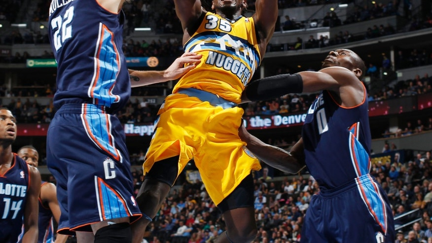 Denver Nuggets forward Kenneth Faried, center, goes up for a shot between Charlotte Bobcats center Byron Mullens, left, and Bismack Biyombo, of the Republic of Congo, in the third quarter of the Nuggets' 110-88 victory in an NBA basketball game in Denver, Saturday, Dec. 22, 2012. (AP Photo/David Zalubowski)