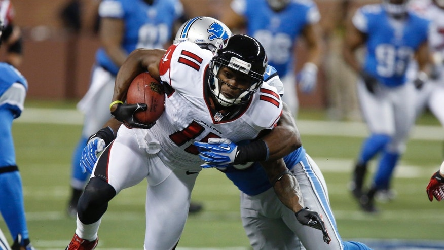 Atlanta Falcons wide receiver Julio Jones (11) tries breaking free from Detroit Lions middle linebacker Stephen Tulloch during the first quarter of an NFL football game at Ford Field in Detroit, Saturday, Dec. 22, 2012. (AP Photo/Duane Burleson)