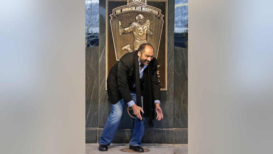 "NFL Hall of Fame running back, Pittsburgh Steelers' Franco Harris stands on the spot where he caught the ""Immaculate Reception"" 40 years ago after a marker was unveiled on the sight  where Three Rivers Stadium once stood on the Northside of  Pittsburgh, Saturday, Dec. 22, 2012. It is the 40th anniversary of the play in which Harris caught a deflected Terry Bradshaw pass intended for Steelers' running back John ""Frenchy"" Fuqua, and returned it 42- yards for a game winning touchdown against the Oakland Raiders. (AP Photo/Gene J. Puskar)"