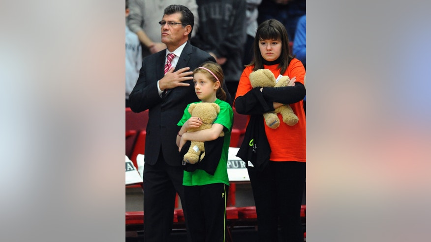 Connecticut head coach Geno Auriemma, left, stands with children from Newtown's Youth Basketball Association during a ceremony for the victims of the Sandy Hook Elementary School shooting before an NCAA women's college basketball game against Hartford, Saturday, Dec. 22, 2012, in West Hartford, Conn. (AP Photo/Jessica Hill)