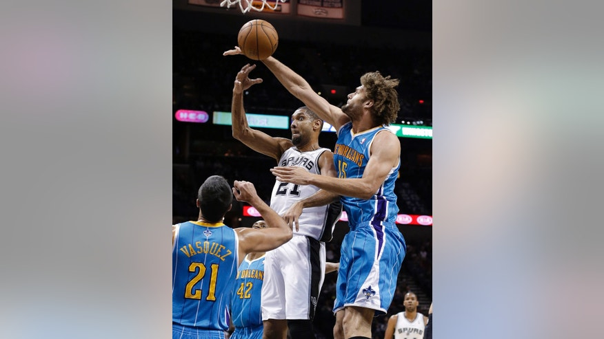 San Antonio Spurs' Tim Duncan (21) passes as New Orleans Hornets' Robin Lopez (15) and Greivis Vasquez (21) defend during the first quarter of an NBA basketball game, Friday, Dec. 21, 2012, in San Antonio. (AP Photo/Eric Gay)
