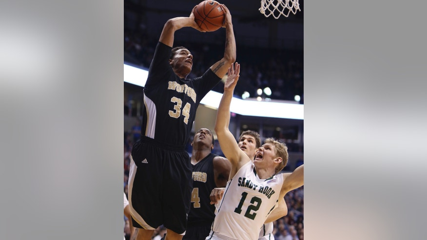 Wofford center Lee Skinner, left, scores over Xavier guard Brad Redford (12) in the second half of an NCAA college basketball game, Saturday, Dec. 22, 2012, in Cincinnati. Wofford won 56-55. (AP Photo/Tony Tribble)