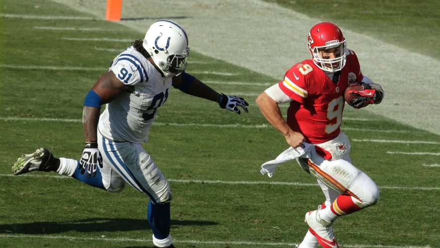 Kansas City Chiefs quarterback Brady Quinn, right, runs from Indianapolis Colts defensive end Ricardo Mathews during the first half of an NFL football game Sunday, Dec. 23, 2012, in Kansas City, Mo. (AP Photo/Charlie Riedel)