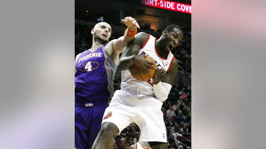 Portland Trail Blazers center J.J. Hickson, right, pulls in a rebound against Phoenix Suns center Marcin Gortat, from Poland, during the first quarter of an NBA basketball game in Portland, Ore., Saturday, Dec. 22, 2012.(AP Photo/Don Ryan)