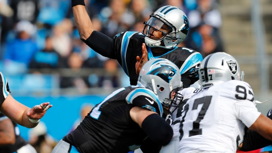 Carolina Panthers' Cam Newton, topr, looks to pass as Oakland Raiders' Andre Carter (97) defends during the first half of an NFL football game in Charlotte, N.C., Sunday, Dec. 23, 2012. (AP Photo/Chuck Burton)