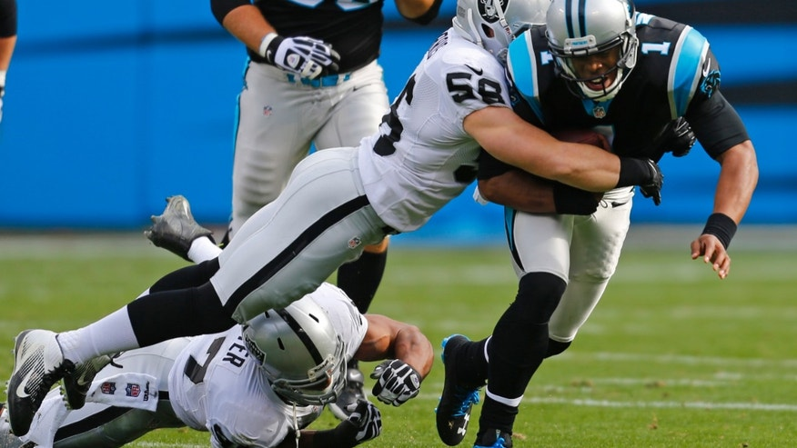Carolina Panthers' Cam Newton (1) is sacked by Oakland Raiders' Miles Burris (56) during the first half of an NFL football game in Charlotte, N.C., Sunday, Dec. 23, 2012. (AP Photo/Chuck Burton)