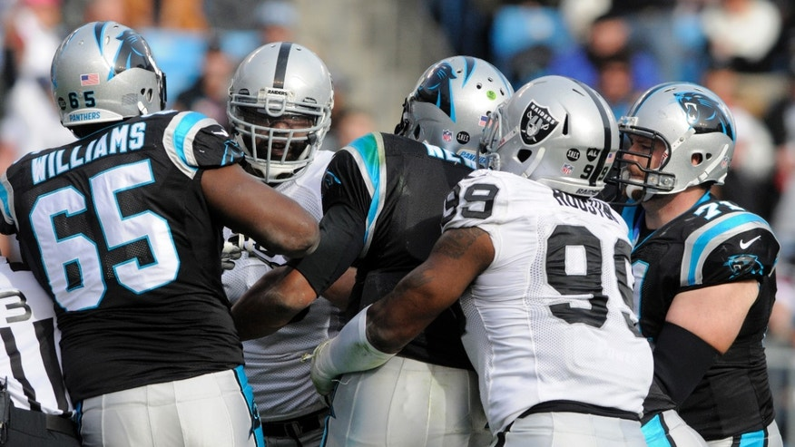 Oakland Raiders' Lamarr Houston, right, holds back Carolina Panthers' Cam Newton, center, as Newton chases after Oakland Raiders' Tommy Kelly, back left, during the first half of an NFL football game in Charlotte, N.C., Sunday, Dec. 23, 2012. (AP Photo/Mike McCarn)