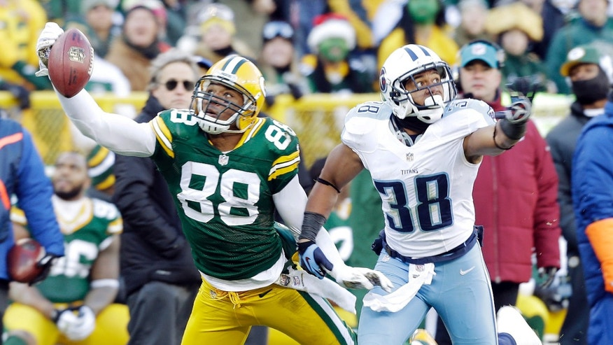 Tennessee Titans' Al Afalava (38) breaks up a pass intended for Green Bay Packers' Jermichael Finley (88) during the first half of an NFL football game Sunday, Dec. 23, 2012, in Green Bay, Wis. (AP Photo/Jeffrey Phelps)