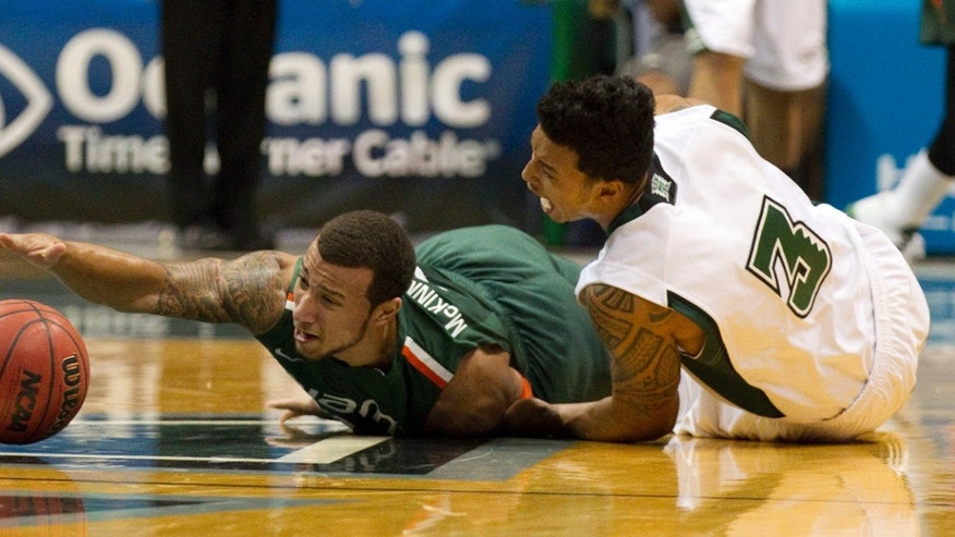 CORRECTS TEAM AND NAME OF PLAYER AT LEFT -  Miami guard Trey McKinney Jones, left, and Hawaii guard Brandon Jawato (3) battle for a loose basketball in the first half of an NCAA college basketball game in the Diamond Head Classic Saturday, Dec. 22, 2012, in Honolulu. (AP Photo/Eugene Tanner)