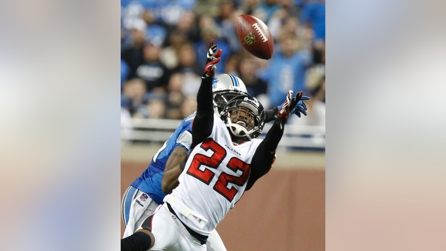 Atlanta Falcons cornerback Asante Samuel (22) intercepts a pass intended for Detroit Lions wide receiver Calvin Johnson, rear, during the fourth quarter of an NFL football game at Ford Field in Detroit, Saturday, Dec. 22, 2012. (AP Photo/Duane Burleson)