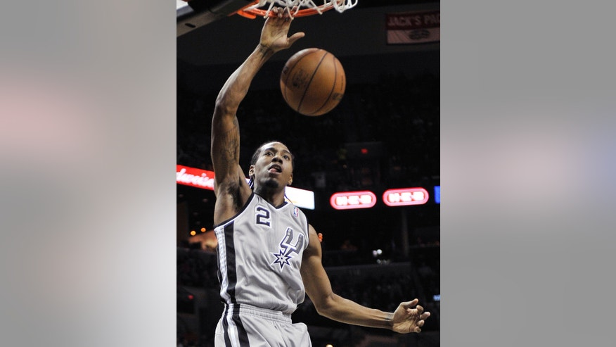 San Antonio Spurs' Kawhi Leonard dunks during the first half of an NBA basketball game against the Dallas Mavericks, Sunday, Dec. 23, 2012, in San Antonio. (AP Photo/Darren Abate)