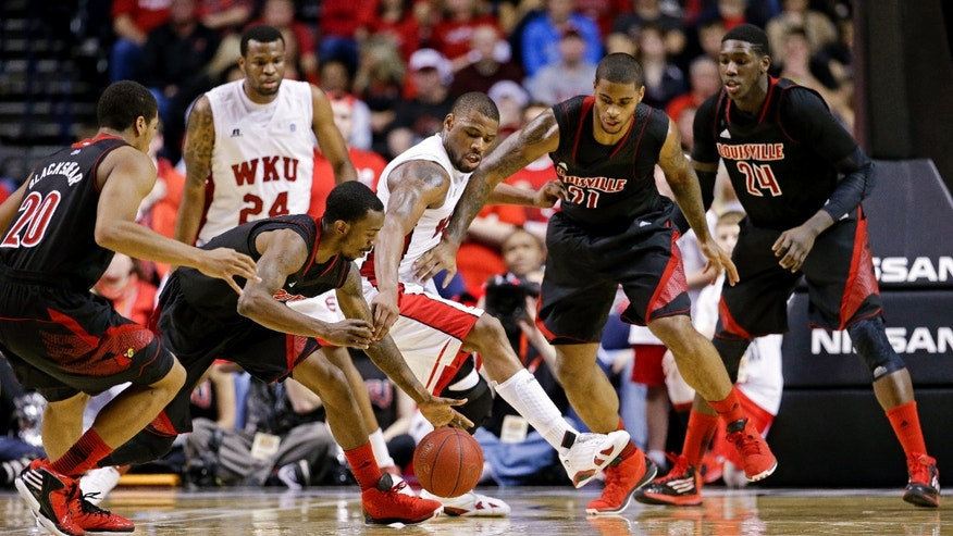 Western Kentucky forward George Fant, center, loses the ball as Louisville defenders Wayne Blackshear (20), Russ Smith, second from left in front, Chane Behanan (21) and Montrezl Harrell (24) surround him in the second half of an NCAA college basketball game on Saturday, Dec. 22, 2012, in Nashville, Tenn. Looking on from behind is Western Kentucky forward Stephon Drane (24). Louisville won 78-55. (AP Photo/Mark Humphrey)