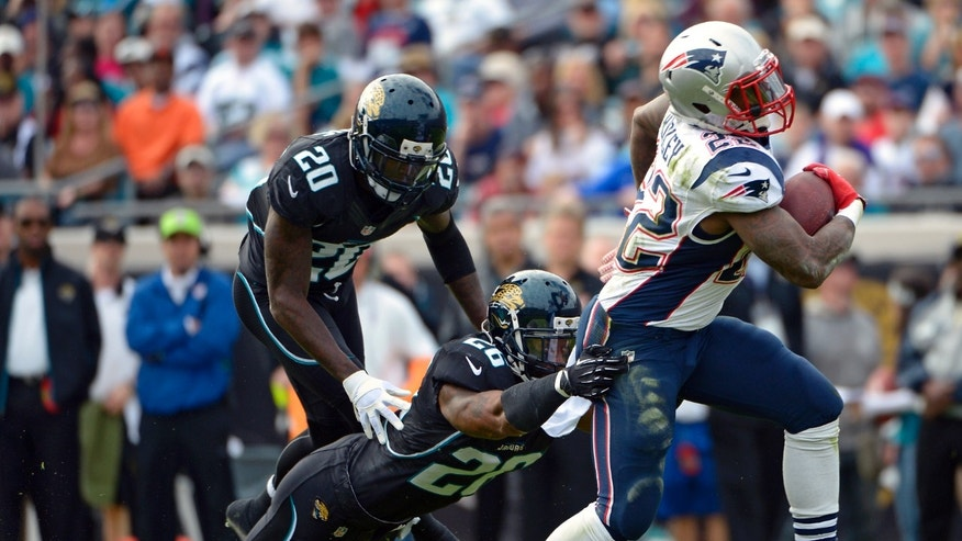 New England Patriots running back Stevan Ridley (22) runs for yardage past Jacksonville Jaguars strong safety Dawan Landry (26) and cornerback Mike Harris (20) during the first half of an NFL football game on Sunday, Dec.  23, 2012, in Jacksonville, Fla. (AP Photo/Phelan M. Ebenhack)