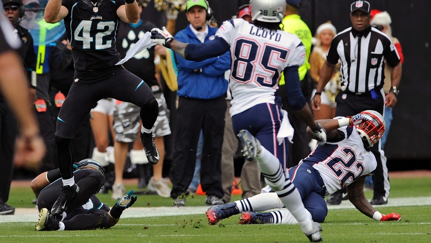 Jacksonville Jaguars free safety Chris Prosinski (42) intercepts a pass in front of New England Patriots wide receiver Brandon Lloyd (85) and running back Stevan Ridley (22) during the first half of an NFL football game on Sunday, Dec.  23, 2012, in Jacksonville, Fla. (AP Photo/Stephen Morton)