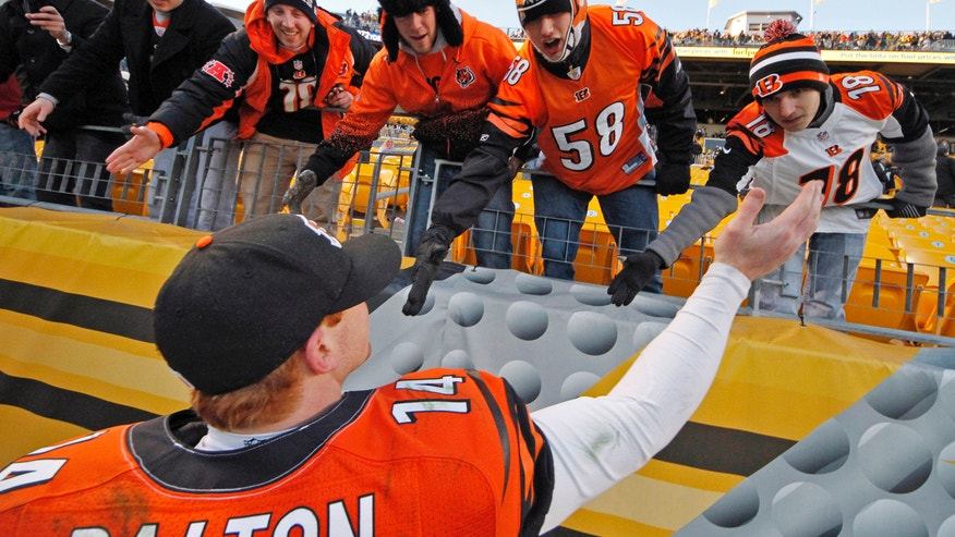 Cincinnati Bengals quarterback Andy Dalton (14) celebrates with Bengals fans as he walks of the field after the team's 13-10 win over the Pittsburgh Steelers in an NFL football game in Pittsburgh, Sunday, Dec. 23, 2012. (AP Photo/Gene J. Puskar)