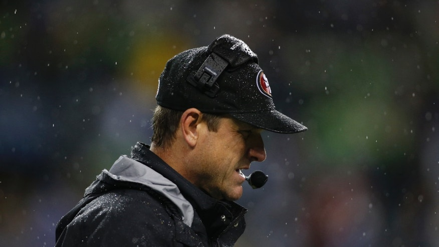 San Francisco 49ers head coach Jim Harbaugh stands in the rain in the second half of an NFL football game against the Seattle Seahawks, Sunday, Dec. 23, 2012, in Seattle. The Seahawks beat the 49ers 42-13. (AP Photo/John Froschauer)