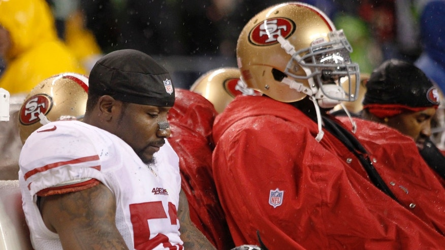 San Francisco 49ers NaVorro Bowman sits on the bench in the final minutes of the 42-13 loss to the Seattle Seahawks in an NFL football game, Sunday, Dec. 23, 2012, in Seattle. (AP Photo/John Froschauer)