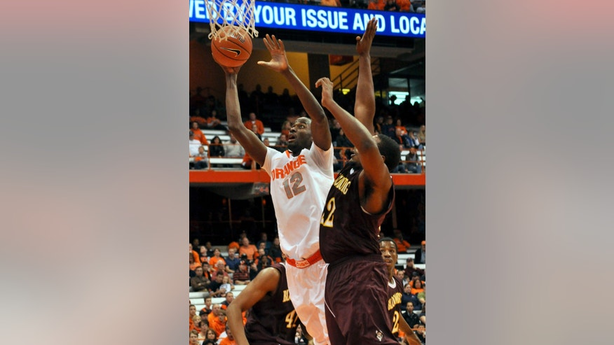 In this Nov. 4, 2012 photo, Syracuse's Baye Moussa Keita (12) scores against Bloomsburg during the second half of an NCAA college exhibition basketball game in Syracuse, N.Y. Keita is from Africa, as is Syracuse football player Siriki Diabate. Soccer, once the mainstay of their lives, is now an afterthought at best. (AP Photo/Kevin Rivoli)