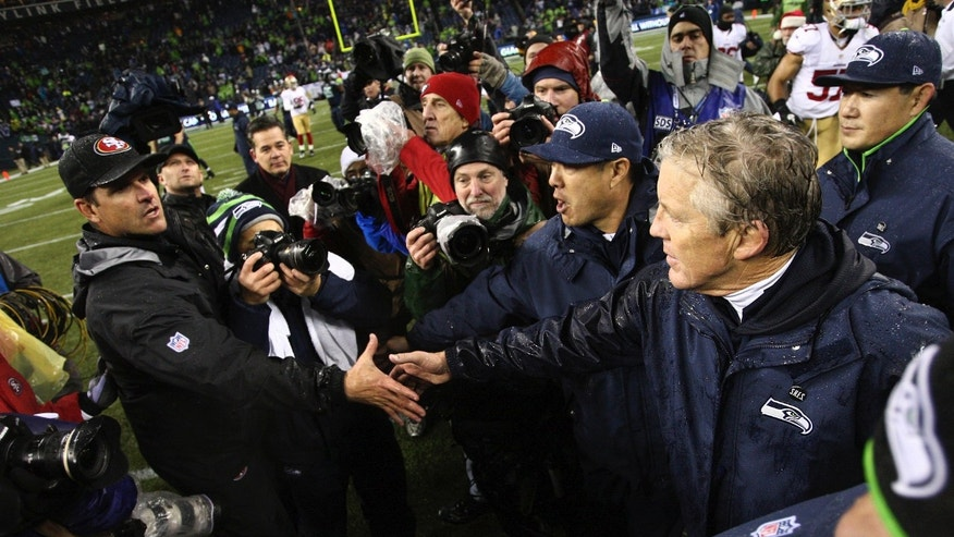 Seattle Seahawks head coach Pete Carroll, right, greets San Francisco 49ers head coach Jim Harbaugh after the game at CenturyLink Field in Seattle, Wash. on Sunday, Dec. 23, 2012. Seattle won 42-13 and clinched a playoff berth. (AP Photo/The Seattle Times, John Lok) SEATTLE OUT; USA TODAY OUT; MAGAZINES OUT; TELEVISION OUT; SALES OUT; MANDATORY CREDIT: JOHN LOK/THE SEATTLE TIMES