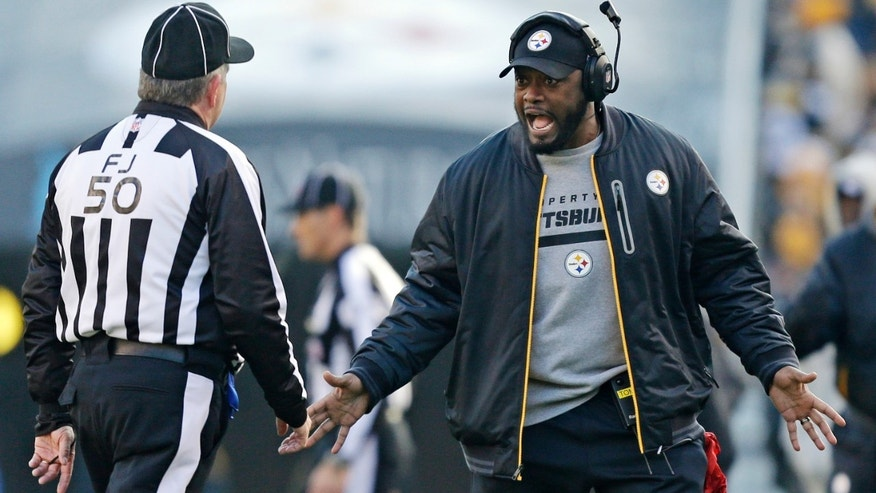Pittsburgh Steelers coach Mike Tomlin, right, makes a point to field judge Mike Weir (50) during the first quarter of an NFL football game against the Cincinnati Bengals in Pittsburgh, Sunday, Dec 23, 2012. The Bengals won 13-10. (AP Photo/Gene J. Puskar)