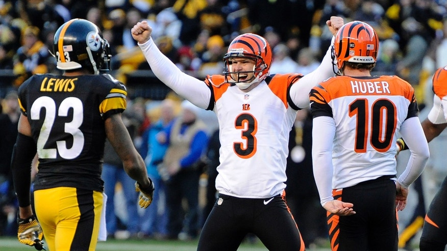 Cincinnati Bengals' Josh Brown (3) celebrates hitting a 43-yard field goal with 4 seconds left in an NFL football game, as Pittsburgh Steelers cornerback Keenan Lewis (23) walks by on Sunday, Dec. 23, 2012, in Pittsburgh. Holder Kevin Huber is at right. The Bengals won 13-10. (AP Photo/Don Wright)