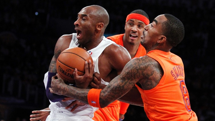 Los Angeles Lakers guard Kobe Bryant, left, is fouled by New York Knicks guard J.R. Smith, right, as forward Carmelo Anthony, center, watches during the first half of their NBA basketball game in Los Angeles, Tuesday, Dec. 25, 2012. (AP Photo/Alex Gallardo)