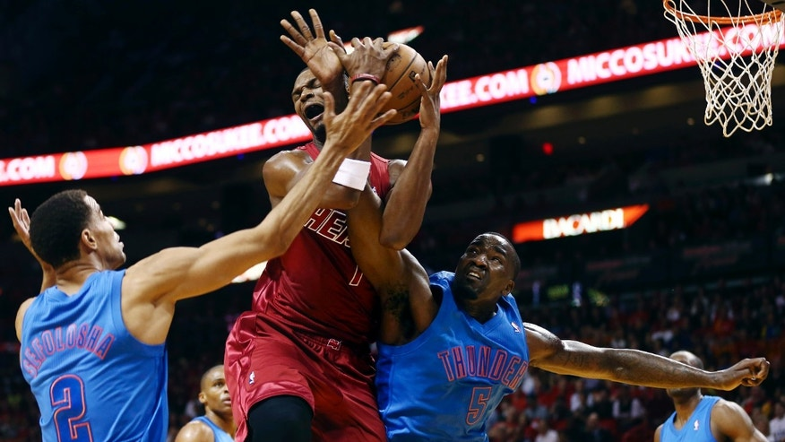Oklahoma City Thunder'S Thabo Sefolosha (2) and Kendrick Perkins (5) defend Miami Heat's Chris Bosh (1) during the first half of an NBA basketball game, Tuesday, Dec. 25, 2012, in Miami. (AP Photo/J Pat Carter)