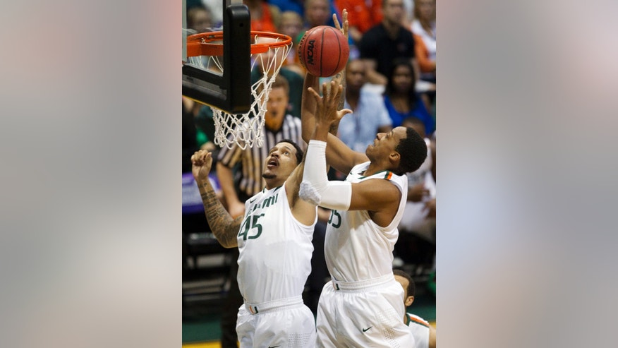 Miami center Julian Gamble (45) and forward Kenny Kadji (35) try to grab a rebound in the first half of an NCAA college basketball game against Indiana State at the Diamond Head Classic, Tuesday, Dec. 25, 2012, in Honolulu. (AP Photo/Eugene Tanner)