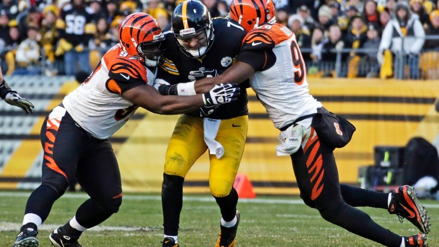Pittsburgh Steelers quarterback Ben Roethlisberger (7) is tackled after a 4-yard scramble, by Cincinnati Bengals defensive tackle Geno Atkins, left, and defensive end Carlos Dunlap during the fourth quarter of an NFL football game in Pittsburgh, Sunday, Dec 23, 2012. The Bengals won 13-10. (AP Photo/Gene J. Puskar)