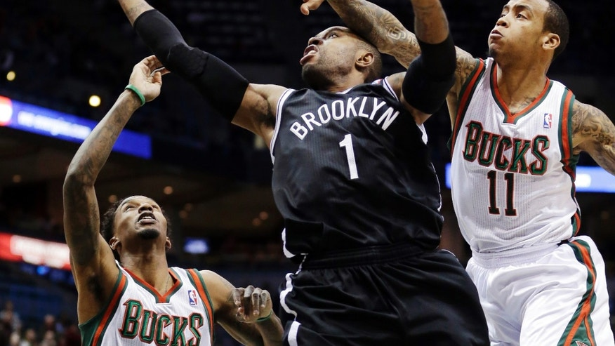 Brooklyn Nets' C.J. Watson (1) shoots between Milwaukee Bucks' Monta Ellis (11) and Brandon Jennings during the first half of an NBA basketball game, Wednesday, Dec. 26, 2012, in Milwaukee. (AP Photo/Morry Gash)