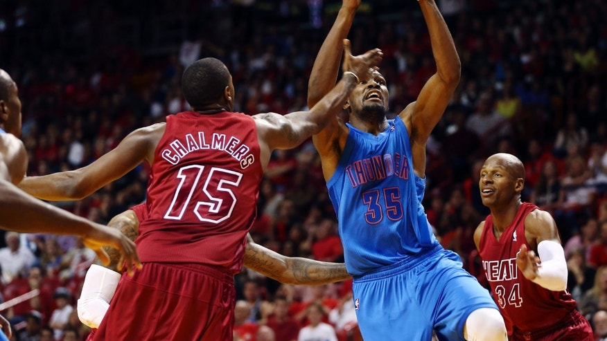 Miami Heat's Mario Chalmers (15) and Ray Allen (34) defend against Oklahoma Cty Thunder's Kevin Durant during the second half of an NBA basketball game in Miami, Tuesday, Dec. 25, 2012. The Heat won 103-97. (AP Photo/J Pat Carter)