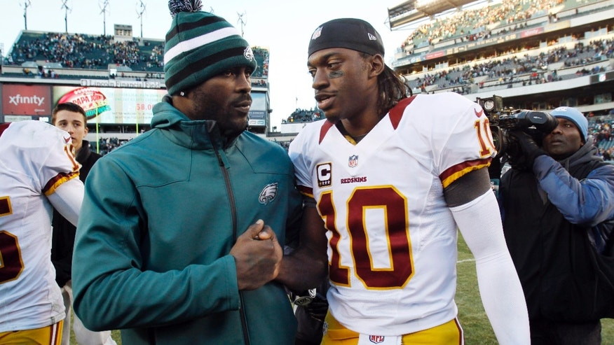 Philadelphia Eagles' Michael Vick, left, and Washington Redskins' Robert Griffin III meet after an NFL football game, Sunday, Dec. 23, 2012, in Philadelphia. Washington won 27-20. (AP Photo/Mel Evans)