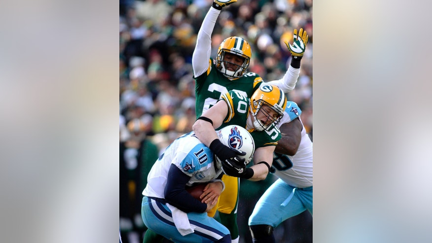 Green Bay Packers linebacker A.J. Hawks (50) sacks Tennessee Titans quarterback Jake Locker (10) as Packers' Casey Hayward comes in to assist in the first quarter of an NFL football game at Lambeau Field in Green Bay, Wis., on Sunday, Dec. 23, 2012. The Packers defeated the Titans 55-7. (AP Photo/Shawano Leader, Cory Dellenbach)