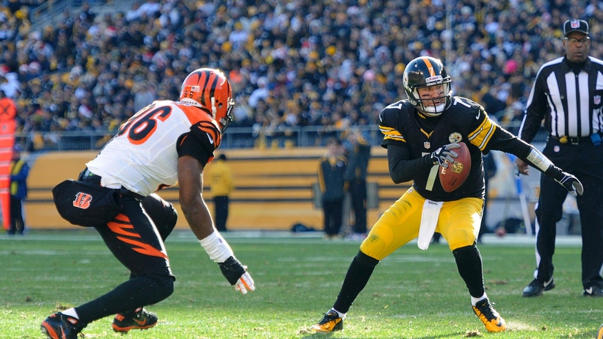 Pittsburgh Steelers quarterback Ben Roethlisberger (7) tries to get away from Cincinnati Bengals defensive end Carlos Dunlap (96) in the second quarter of an NFL football game Sunday, Dec. 23, 2012, in Pittsburgh. (AP Photo/Don Wright)