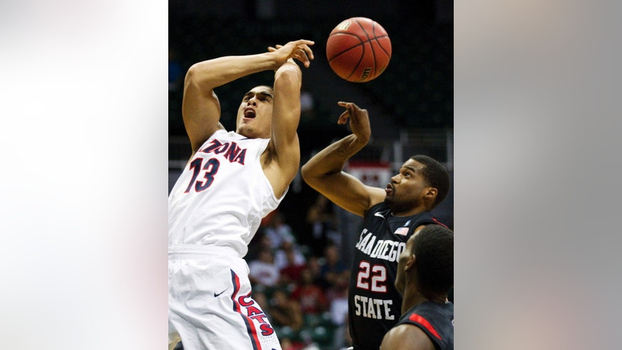 Arizona guard Nick Johnson (13) has the basketball stripped away from behind by San Diego State guard Chase Tapley (22) in the first half of an NCAA college basketball game at the Diamond Head Classic, Tuesday, Dec. 25, 2012, in Honolulu. (AP Photo/Eugene Tanner)