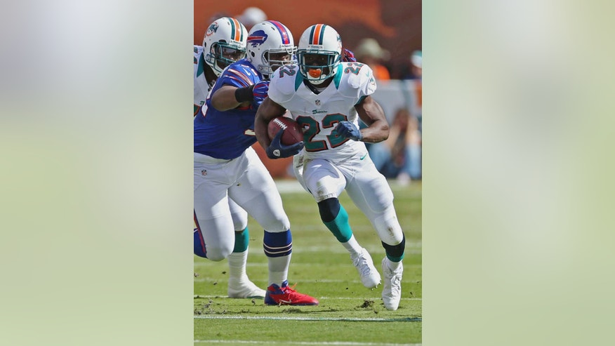 Miami Dolphins running back Reggie Bush (22) gets away from Buffalo Bills defensive end Alex Carrington (92) during the first half of an NFL football game on Sunday, Dec. 23, 2012, in Miami. (AP Photo/J Pat Carter)