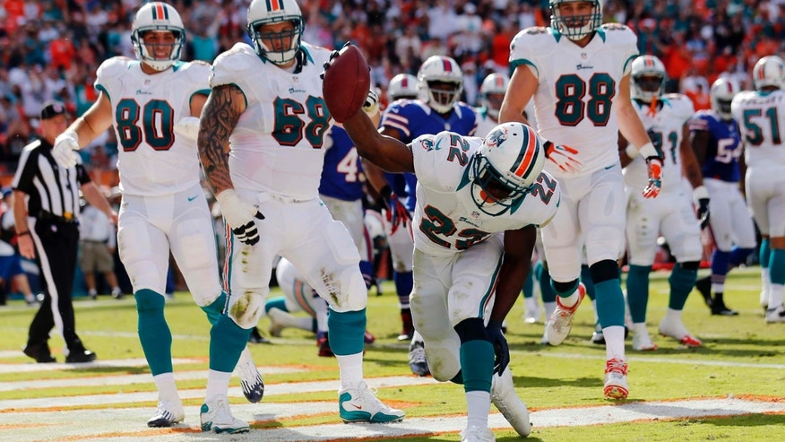 Miami Dolphins running back Reggie Bush (22) spikes the ball after a touchdown during the first half of an NFL football game against the Buffalo Bills, Sunday, Dec. 23, 2012, in Miami. (AP Photo/John Bazemore)