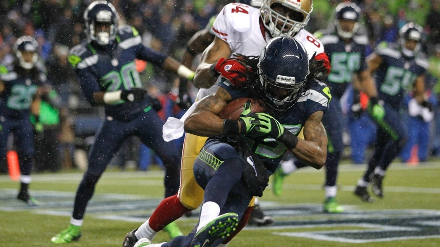 Seattle Seahawks' Richard Sherman comes down with an interception ahead of San Francisco 49ers' wide receiver Randy Moss in the second half of an NFL football game, Sunday, Dec. 23, 2012, in Seattle. The Seahawks beat the 49ers 42-13. (AP Photo/John Froschauer)