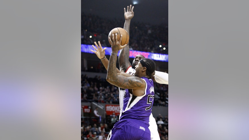Sacramento Kings forward James Johnson, right, drives to the basket against Portland Trail Blazers center J.J. Hickson during the first quarter of an NBA basketball game in Portland, Ore., Wednesday, Dec. 26, 2012. (AP Photo/Don Ryan)