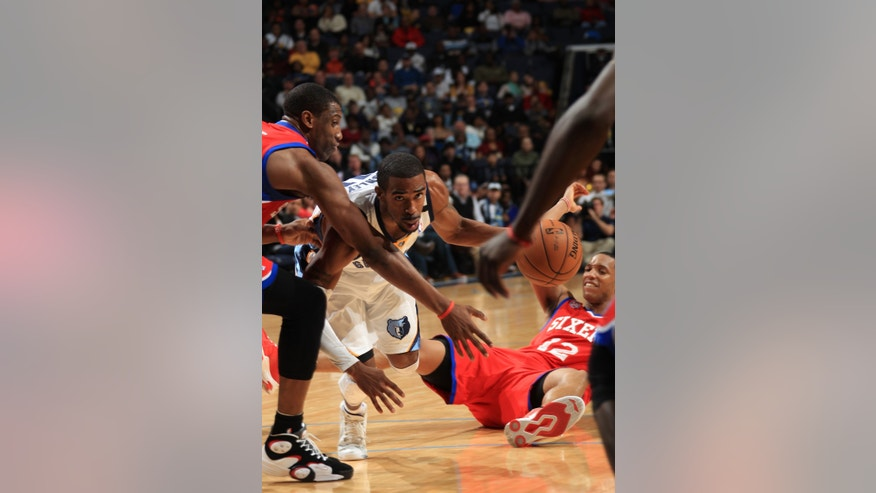 Memphis Grizzlies guard Mike Conley, center, grabs a loose ball defended by  Philadelphia 76ers forwards Thaddeus Young, left, and Evan Turner (12) in the first half of an NBA basketball game on Wednesday, Dec. 26, 2012, in Memphis, Tenn. (AP Photo/Nikki Boertman)